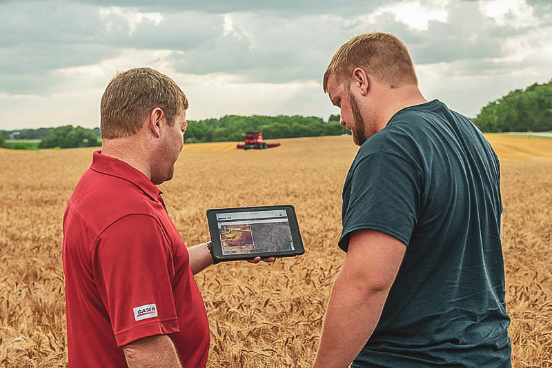 Precision Farming Specialist with grower in wheat field with Case IH combine in background