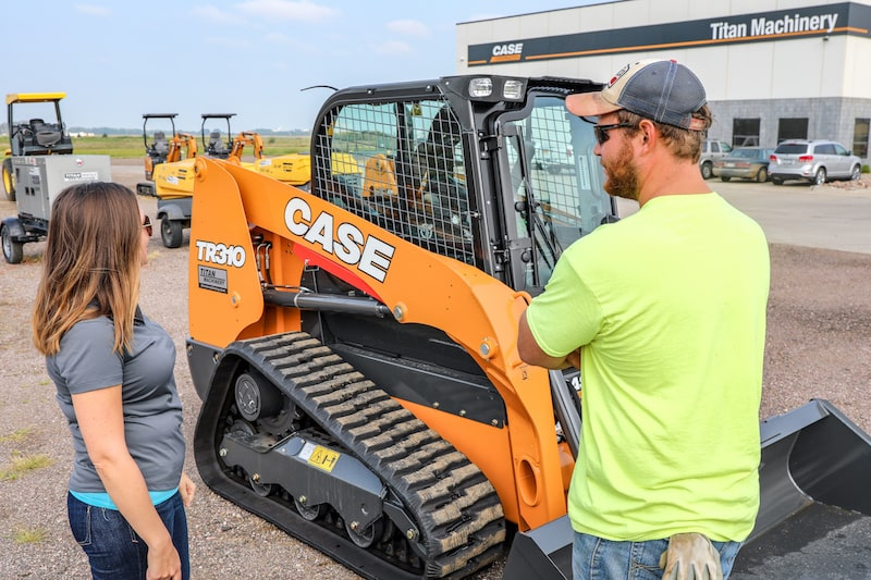 Rental equipment sales consultant talking with customer by Case skid steer