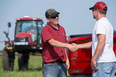 Equipment sales consultant shaking hands with customer in field with sprayer