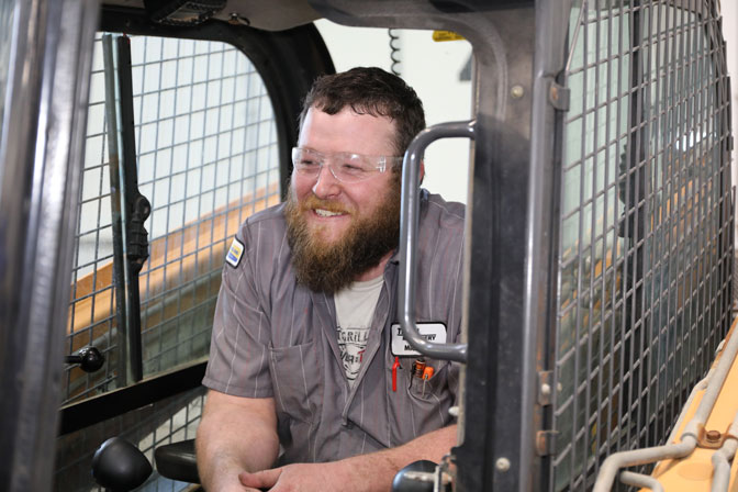 Happy service technician sitting in Case skid steer