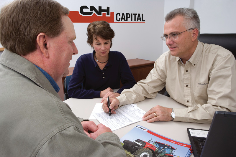 Customer signing equipment insurance plan with CNH Capital logo in background