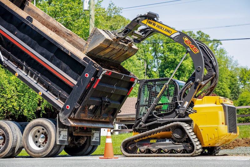 New Holland Construction C245 skid steer dumping into truck