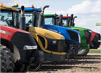Case IH, CAT, New Holland, and John Deere tractors lined up