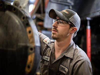 Service Technician working on Case IH equipment with a grinder